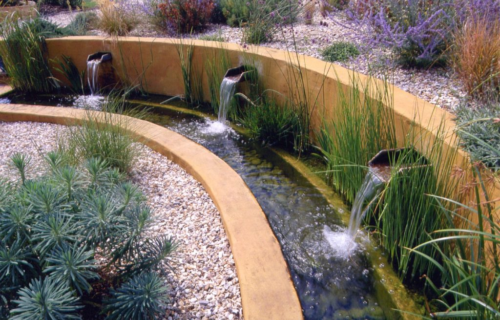 This small rill incorporates a bio-filter alongside the wall. Spouts pour water into the filter, where it is cleansed before being passed back into the rill.